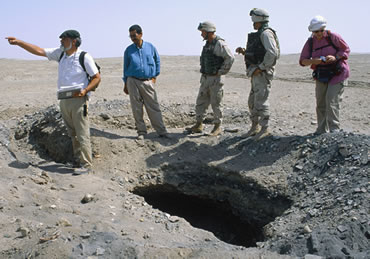 Archaeologists and soldiers examine a fresh looter's pit at the ancient Mesopotamian city of Larsa