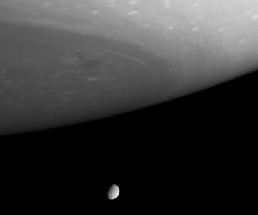 Saturn's south pole can be seen swathed in clouds and ribbons of gas with the icy moon Tethys below