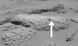 The hole left by the rover's rock abrasion tool is arrowed