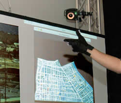 Mounted above the large display area, the camera tracks hand movements while a computer interprets the gestures