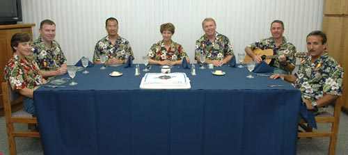Wearing the traditional Hawaiian shirts, Discovery's crew gathers for the traditional cake before suiting up for launch