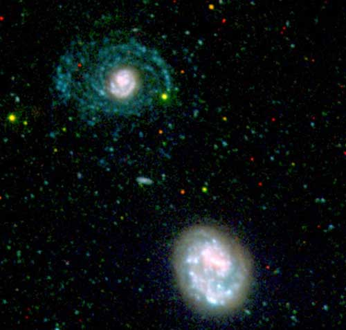 Interaction with the galaxy NGC 4618 (bottom) may have spurred the formation of hot, newborn stars in the galaxy NGC 4625 (top). The stars form large spiral arms (blue) that are only visible at ultraviolet wavelengths