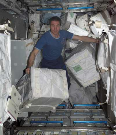 Space station Commander Sergei Krikalev gathers some of the many packages by space shuttle Discovery