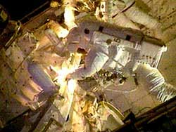 Astronaut Steve Robinson emerges from space shuttle Discovery's airlock to begin the third spacewalk