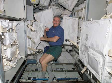Astronaut John Phillips moves supplies and equipment from the Italian cargo module