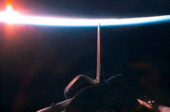 A sunrise dissecting a line of airglow of Earth's atmosphere provides the backdrop for the shuttle after departure from the International Space Station