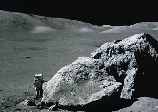 Scientist-astronaut Harrison H Schmitt stands next to a huge, split boulder during the Apollo 17 mission