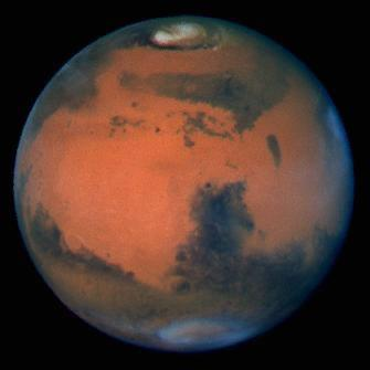 This Hubble image is the sharpest view of Mars ever taken from Earth – the Martian north pole is at the top, near the centre of the bright polar cap