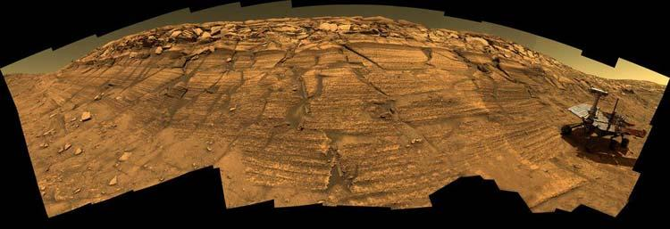 This constructed image shows Opportunity exploring the layered rocks on the inner wall of Endurance Crater