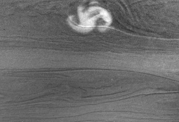 Light reflected from Saturn's rings provided enough illumination for Cassini's cameras to snap clouds from the mega-storm on 27 January 2006, even though Cassini was in the planet's shadow
