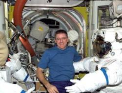 Bill McArthur works with spacesuits in the station's Quest airlock