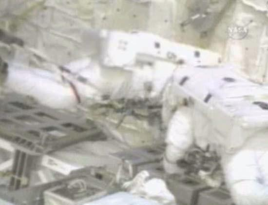 Astronauts Piers Sellers (left) and Mike Fossum repair pre-damaged heat shield panels in the shuttle's payload bay