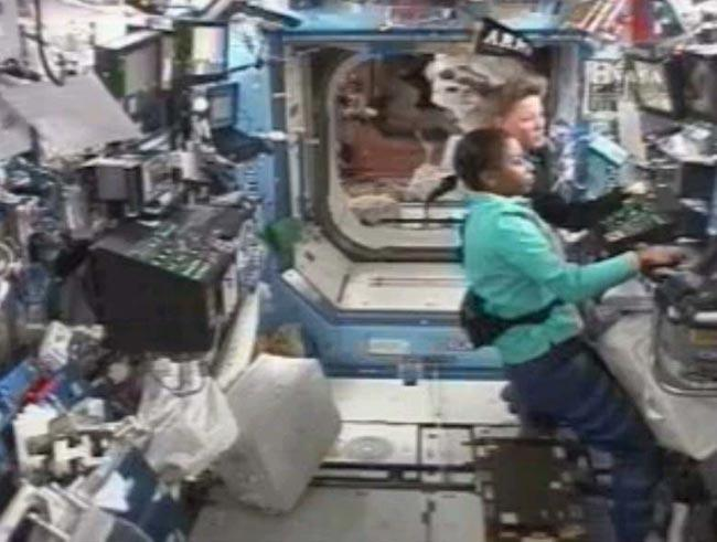 Stephanie Wilson (front) and Lisa Nowak used the space station's robotic arm to put a cargo module back into the shuttle on Friday