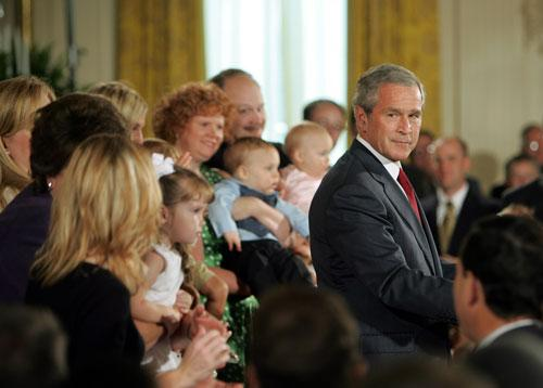 Family members who have adopted frozen embryo babies applaud President Bush as he makes remarks on embryonic stem cell research in the East Room of the White House in Washington, on 19 July
