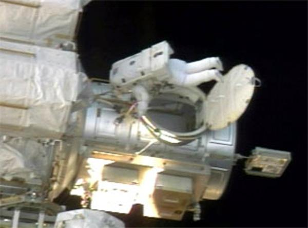 Astronaut Heidemarie Stefanyshyn-Piper exits the airlock of the ISS to begin the shuttle mission's third spacewalk on Friday