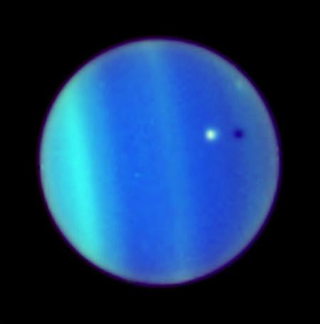 The icy moon Ariel (white) casts a shadow on the cloud tops of Uranus - the moon is named for a mischievous spirit in Shakespeare's The Tempest