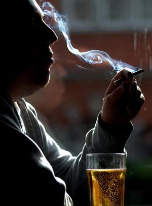 Man with beer glass smoking a cigarette