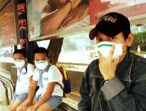 Children wearing protective masks at a bus stop in Kuala Lumpur, Malaysia, following an outbreak of bird flu, February 2006