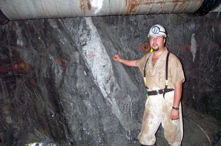 About 2 miles below the ground in a South African gold mine stands Duane Moser next to the fracture zone (white area) where the one-of-a-kind bacteria were found