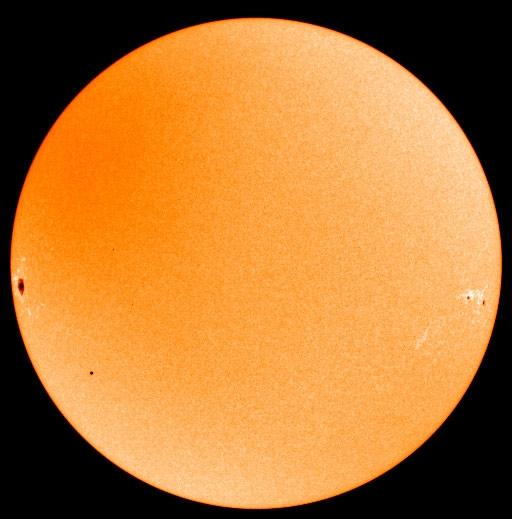 Mercury appears as a miniscule black spot at lower left, dwarfed by a large sunspot at mid left in this visible light SOHO image. Two more sunspots appear at mid right