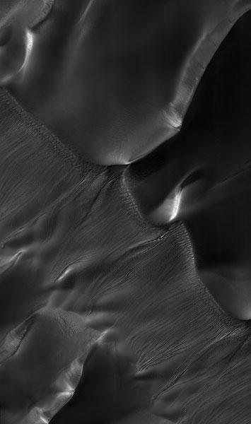 These gullies on the sides of sand dunes, first imaged by the Mars Global Surveyor, but seen in much greater detail by MRO may have formed when sunlight evaporated frozen carbon dioxide or water mixed in with the sand, causing avalanches