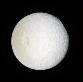 Saturn's moon Tethys bears the brunt of the particles spewing from its neighbour Enceladus – these particles seem to keep its surface clean and bright