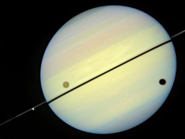 From left to right, the moon Tethys (bright dot near rings), the large moon Titan and its shadow appear in this image of Saturn taken by the Hubble Space Telescope