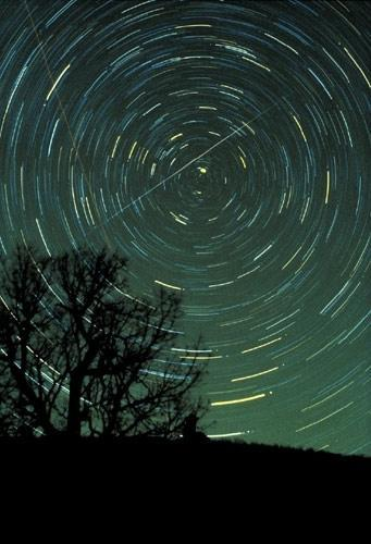 A meteor streaks across the sky against a background of star trails in this long-exposure image taken in 1985 during the Geminid shower