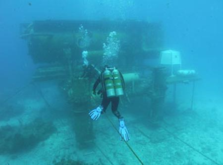 NEEMO 12 crew members swim to their undersea habitat during a training session