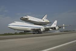 The 747 jumbo jet carrying the shuttle Atlantis makes a smooth touchdown at Florida's Kennedy Space Center