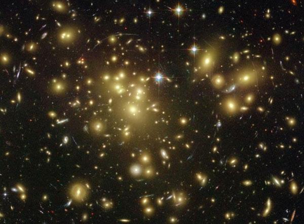 Astronomers used the gravity of nearby clusters of galaxies as cosmic magnifying glasses to search for much more distant galaxies. This gravitational lensing effect is seen here in the vicinity of the galaxy cluster Abell 1689, where some background galaxies are distorted into arcs