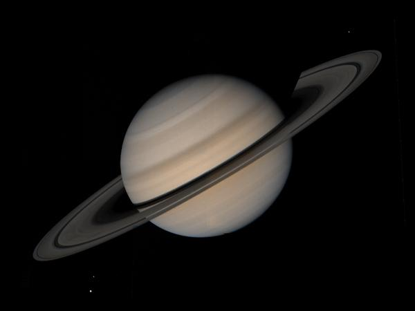 Centrifugal forces from Saturn's rotation make the planet egg-shaped, with flattened poles and a bulge at the equator, as seen in this Voyager 1 portrait