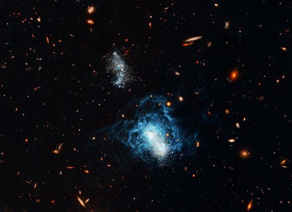 The galaxy I Zwicky 18 is made up of two sections - the brighter, main body at lower right, and a secondary body at upper left. It is not clear whether the secondary body was once a separate galaxy that merged with the main one, setting off a burst of new star formation