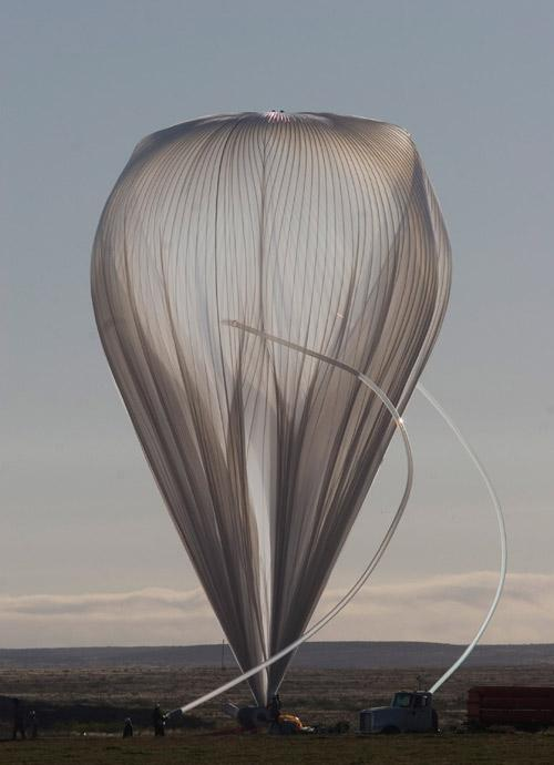 Slender hoses, blown into arcs by the wind, partially filled the Sunrise project's balloon with helium before launch on 3 October. Much of the balloon - which is larger than a jumbo jet - is left unfilled so it can expand as it rises into the stratosphere, where air pressure is lower