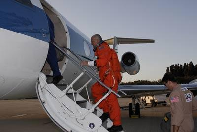 Astronaut Alan Poindexter, the mission's pilot, climbs into a shuttle training aircraft to begin practice landings at NASA's Kennedy Space Center