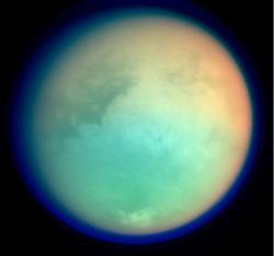 Conditions suitable for life may prevail in the ocean of liquid water beneath the icy surface of Saturn's largest moon, Titan, seen here in a false-colour image taken by the Cassini spacecraft