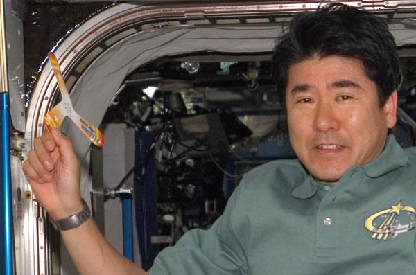 Astronaut Takao Doi holds the three-bladed paper boomerang he threw inside the International Space Station