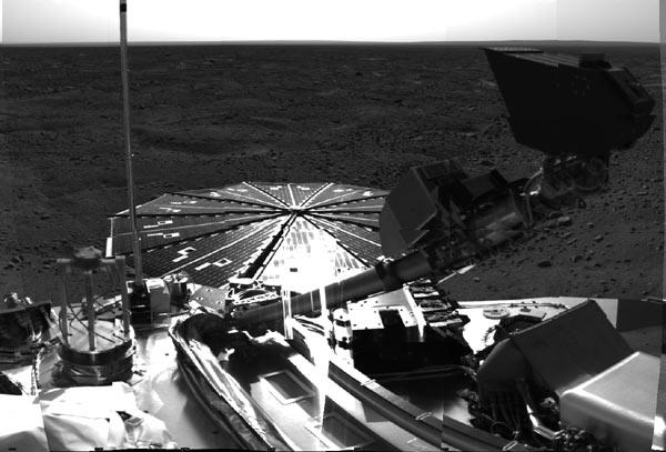 The robotic arm on Phoenix salutes the Martian landscape, with the scoop appearing as a large dark shape just below the horizon and above the lander's deck