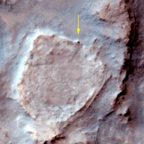 The Spirit rover (dark spot marked with arrow) spent the winter parked on the northern edge of a volcanic plateau called Home Plate