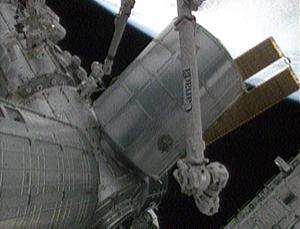 Astronauts inside the space station used a robotic crane to remove a cargo canister from the shuttle's payload bay and fly it to a berthing port on the station