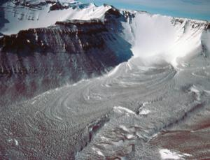 Debris flows, like the one shown here above a glacier in Antarctica's Friedman Valley, are also found on Mars. A new study suggests the features hide large ice deposits