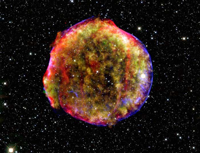 Tycho's supernova left behind an expanding cloud of super-hot debris, which appears green and yellow in this composite X-ray and infrared image stitched together from data from the Spitzer and Chandra space observatories and the Calar Alto observatory in Spain