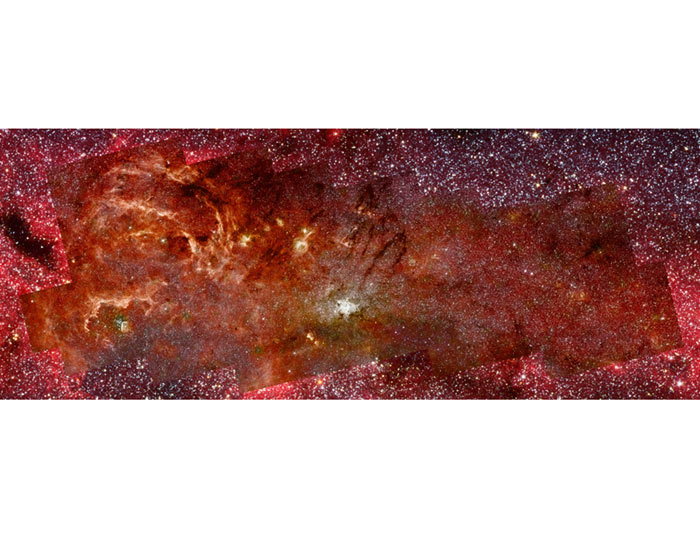 This portrait of the Milky Way's central region was made by combining images taken by Hubble's Near Infrared Camera and Multi-Object Spectrometer (NICMOS) between February and June 2008 and images previously taken by Spitzer's Infrared Astronomy Camera (IRAC). The region at lower left shows pillars of gas sculpted by winds from hot, massive stars in the Quintuplet cluster. At the centre of the image, ionised gas surrounding the supermassive black hole at the galactic centre is confined to a bright spiral embedded within a doughnut-shaped ring of gas and dust. (Hubble image: NASA/ESA/Q D Wang/UMass Amherst; Spitzer image: NASA/JPL/S Stolovy/Spitzer Science Center/Caltech)