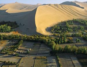As deserts encroach on fertile land, as it has near Dunhuang, China, people will be forced to move towards the poles