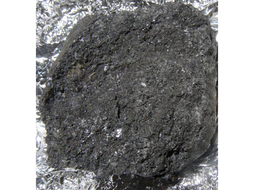 The recovered bits of asteroid 2008 TC3, like the meteorite shown here, typically have a dark, scruffy texture. They are eurelites, a type of meteroite that is only partially melted. By comparing the spectrum of the meteorites with observations of 2008 TC3 while it was still approaching Earth, astronomers can now link eurelites with dark, F-class asteroids. This is the first time rocks that have fallen to Earth have been definitively matched up with a particular class of parent asteroids