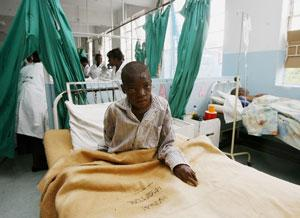 A Zimbabwean cholera patient sits in his bed at a hospital in Harare in 2009