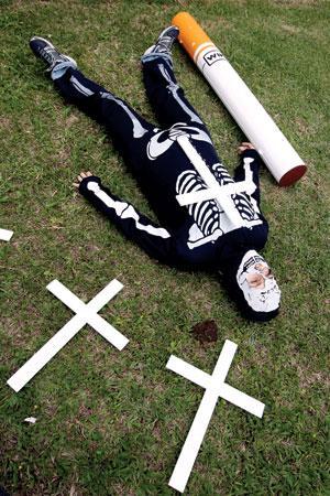 An anti-smoking activist plays dead on November 11, 2008 during a demonstration near São Paulo State Legislative Assembly, in São Paulo, southeastern Brazil (Image: Sérgio Castro / Agência Estado / AE / Image Forum