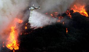 A helicopter makes a water drop over flames along a ridge in Placerita Canyon, California, in November 2008
