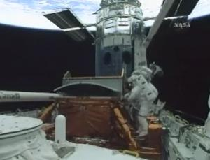 Astronauts John Grunsfeld and Andrew Feustel installed a new camera and data router on the Hubble Space Telescope during the first spacewalk of the last Hubble servicing mission. The 7 hour, 20 minute spacewalk took almost an hour longer than scheduled