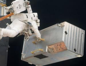 Anchored to the space shuttle's robotic arm on Saturday, astronaut Andrew Feustel carries a corrective optics box that was removed from the telescope